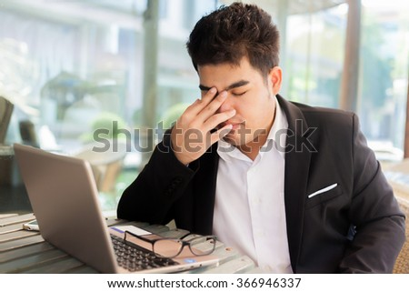 Young Asian businessman suffering from tired eyes after long hours of using laptop. - stock photo