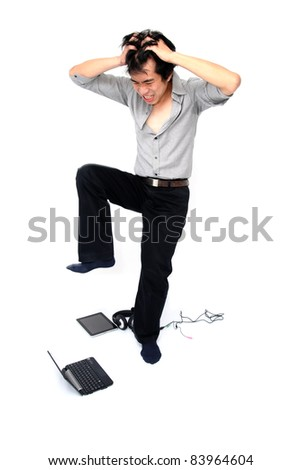 Young asian businessman trying to crunch his laptop - stock photo
