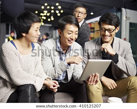 young asian businesspeople sitting in sofa looking at tablet computer, happy and smiling. - stock photo