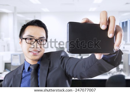 Young asian businessperson using his mobile phone to take self picture in the office - stock photo