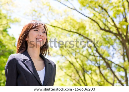young asian businesswoman in the park - stock photo