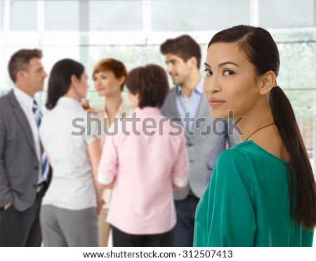 Young asian businesswoman looking back business team in background. - stock photo