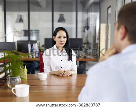 young asian businesswoman looking serious and nervous during a job interview. - stock photo