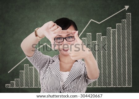 Young asian businesswoman making a hand frame - stock photo