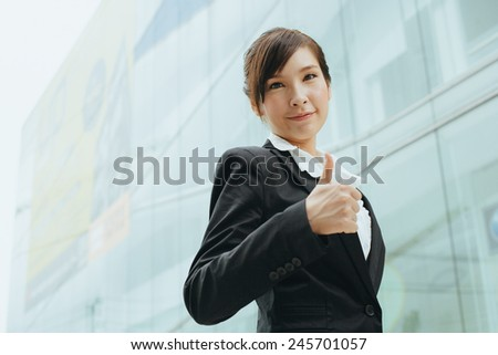 Young asian businesswoman shows her thumb up. - stock photo