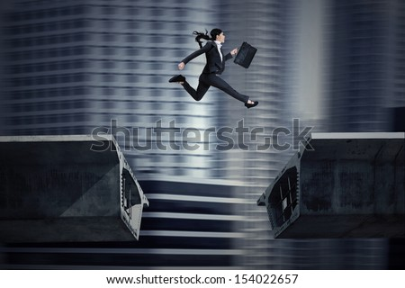 Young asian businesswoman with briefcase jumping over a gap in the bridge - stock photo