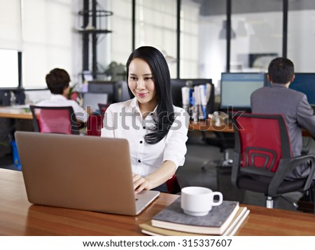 young asian businesswoman working in office using laptop computer with colleagues in background. - stock photo