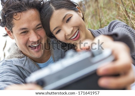 Young Asian Chinese man & woman, boy & girl, couple sitting in the sand dunes on a beach taking a selfie photograph with retro style digital camera - stock photo