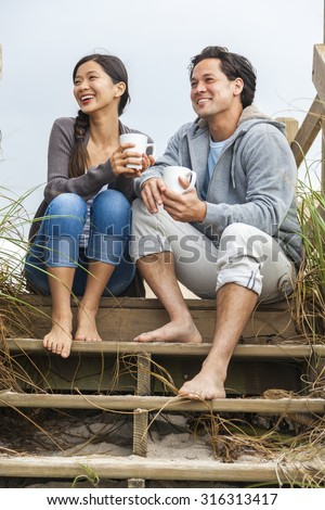 Young Asian Chinese man & woman, boy & girl, couple sitting on wooden steps overlooking a beach drinking mugs of tea or coffee - stock photo