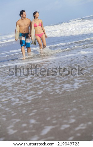 Young Asian Chinese man & woman, boy & girl, surfing couple on a beach with surfboards - stock photo