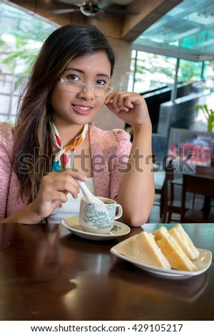 Young Asian college girl student sitting on campus cafe, breakfast with coffee and sandwish, smile, feel relax and enjoy - stock photo