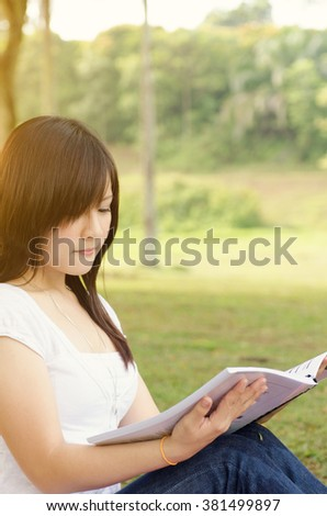 Young Asian college girl student sitting on campus lawn and reading book. - stock photo