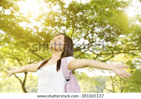 Young Asian college girl student standing on campus lawn, arms outstretched and smiling. - stock photo