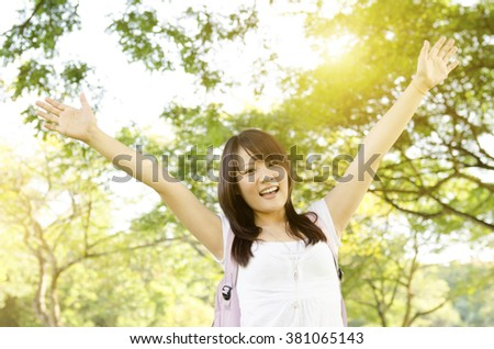 Young Asian college girl student standing on campus lawn, open arms and smiling. - stock photo