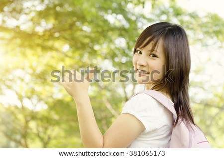 Young Asian college girl student standing on campus lawn, showing thumb up and smiling. - stock photo