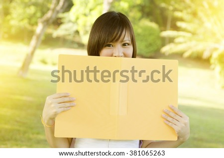 Young Asian college girl student standing on campus lawn, smiling and covered face by file folder. - stock photo