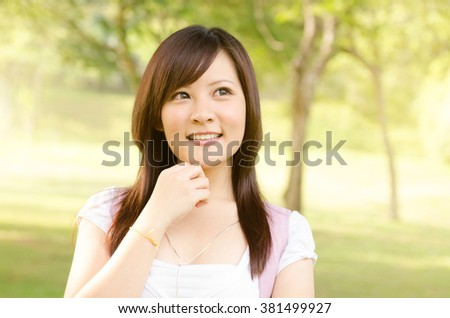 Young Asian college girl student standing on campus lawn, thinking and looking away. - stock photo