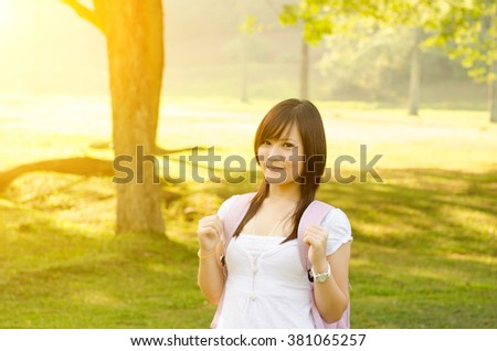 Young Asian college student standing on campus lawn, with backpack and smiling. - stock photo
