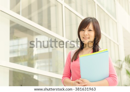 Young Asian college student standing outside campus building, holding file folder and smiling. - stock photo