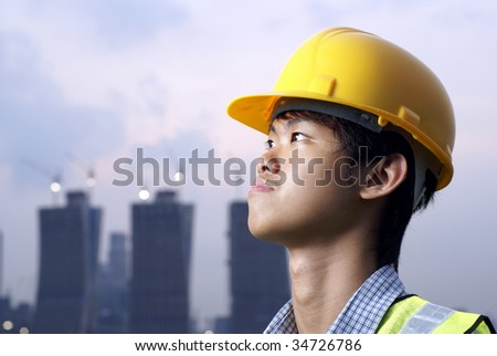 Young asian construction engineer looking up wearing yellow hardhat - stock photo