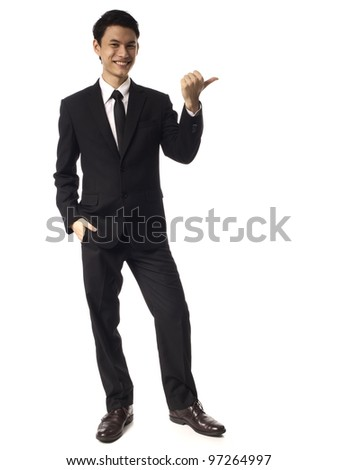 Young Asian Corporate Man pointing with thumb over white background - stock photo