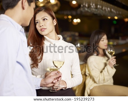 young asian couple having a conversation in bar. - stock photo