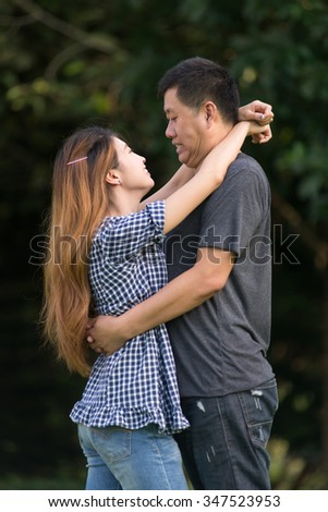 young Asian couple smile and hug each other with romantic mood and tone effect for conceptual use as wedding, romantic, loves, emotion, use purpose - stock photo