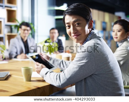 young asian designer business man looking at camera smiling during meeting. - stock photo