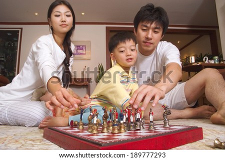 Young Asian family playing chess on the floor - stock photo