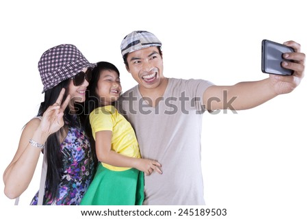 Young asian family using camera phone to take self portrait together in the studio - stock photo