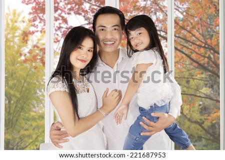 Young asian family with three member smiling at camera under autumn tree - stock photo