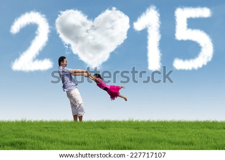 Young asian father swing his daughter in meadow under cloud of 2015 - stock photo