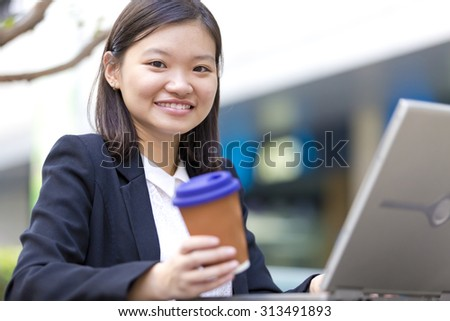 Young Asian female executive drinking coffee and using laptop PC - stock photo