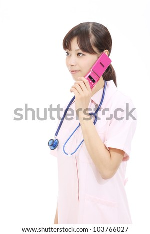 Young asian female nurse calling by cellular phone - stock photo