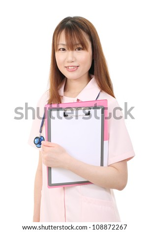 Young asian female nurse holding a clipboard - stock photo