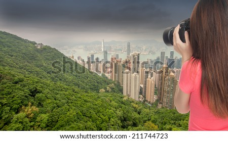 Young asian female photographer taking a picture of Hong Kong skyline - stock photo