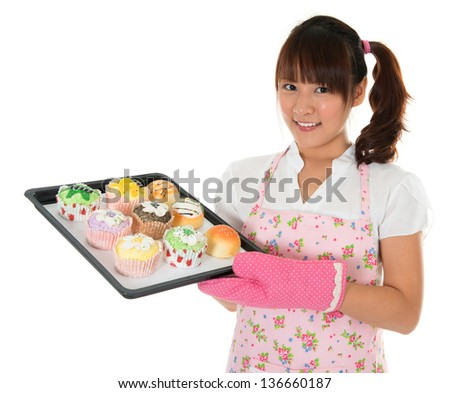 Young Asian girl baking bread and cupcakes, wearing apron and gloves holding tray isolated on white. - stock photo