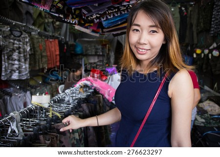 Young asian girl in local shop buying clothes - stock photo