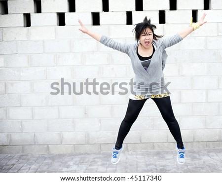 Young asian girl jumping in gym clothes - stock photo