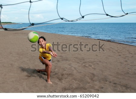 young asian girl playing beach volleyball - stock photo