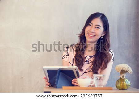 Young Asian girl use tablet for search information in coffee shop - stock photo