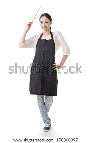 Young Asian housewife hold a chopsticks in apron, full portrait isolated on white background. - stock photo