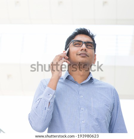 Young Asian Indian business executive on the phone, modern building at background. - stock photo