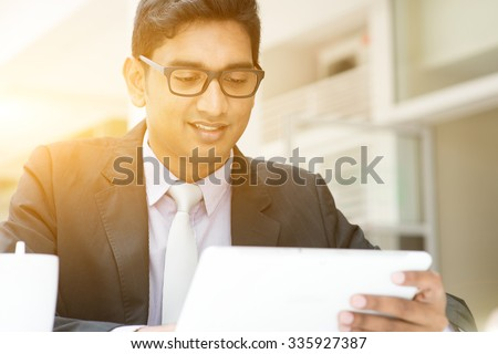 Young Asian Indian business people using tablet pc at cafe, relaxing with a cup of coffee. India male business man, modern office building with sunlight as background. - stock photo