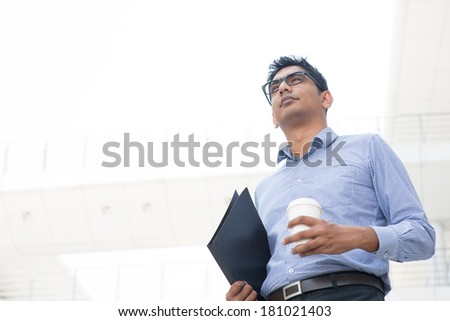 Young Asian Indian businessman holding a cup of coffee looking away, India male business man, real modern office building as background. - stock photo