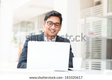Young Asian Indian businessman using a notebook computer or laptop during office break at cafe, relaxing with a cup of coffee. India male business man, real modern office building as background. - stock photo