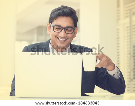 Young Asian Indian businessman using a notebook computer or laptop during office break at cafe, relaxing with a cup of coffee. India male business man, in vintage retro effect. - stock photo