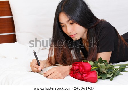 young asian lady writing a letter on bed  - stock photo