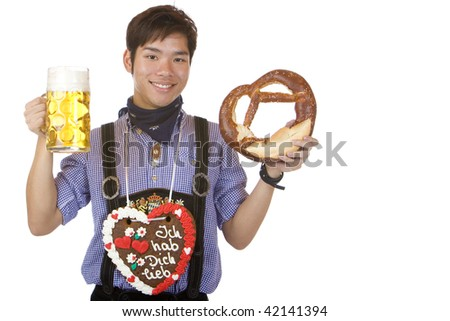 Young Asian man having gingerbread heart around neck and holds beer stein and Pretzel. Isolated on white. - stock photo