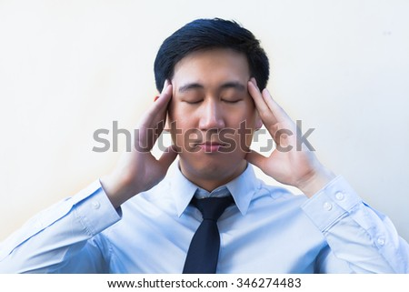 Young Asian man having headache / stress / overworked in office - stock photo